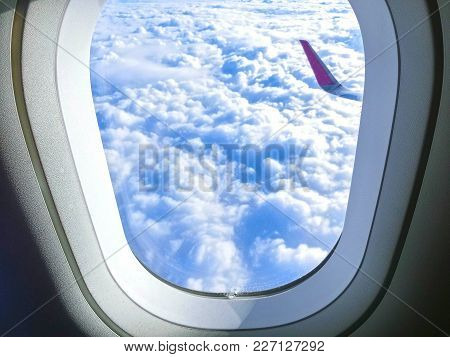 View Of Wing Of An Airplane Flying Above The Clouds. Clouds And Blue Sky Through An Airplane Window