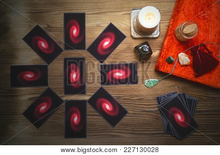 Tarot Cards Deck And Book Of Magic On Fortune Teller Desk Table Background. Future Reading Concept.