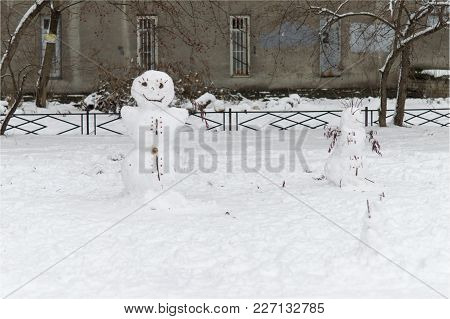 Cheerful Snowmen From The Snow Stand In The Courtyard Of A House In The City And Smile.