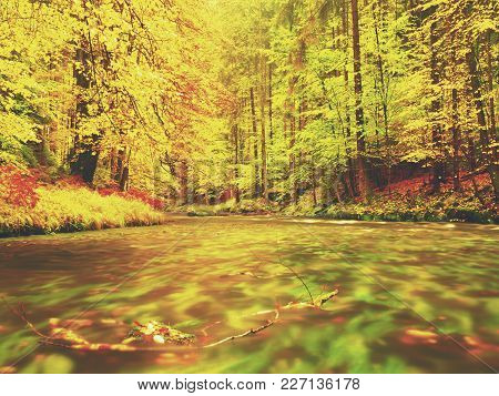 Dreamy Sunset Above Mountain In Autumn Forest. Colorful Mist Between Trees On River Banks. Autumnal