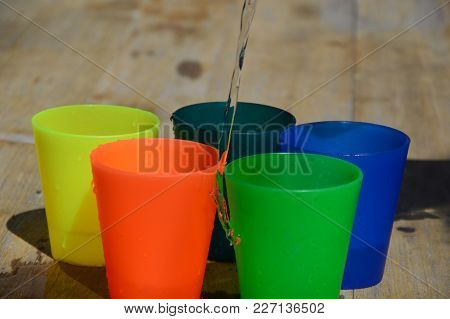 Colorful Plastic Cups On A Wooden Table, Filled With Water