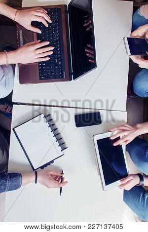 View From Above. A Team Of People Discussing The Work. In The Hands Of A Notebook, A Mobile Phone, A
