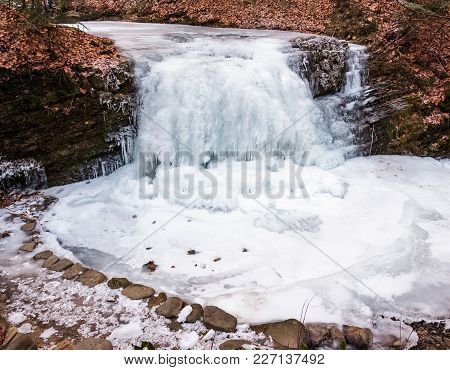 Frozen Waterfall On The  River Among Forest With Brown Foliage On The Ground