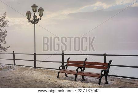 Bench And Lantern On Foggy Winter Morning. Location Nezalezhnosti Embankment Uzhgorod, Ukraine