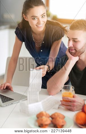 Couple Paying Their Bills With Laptop In Kitchen At Home.