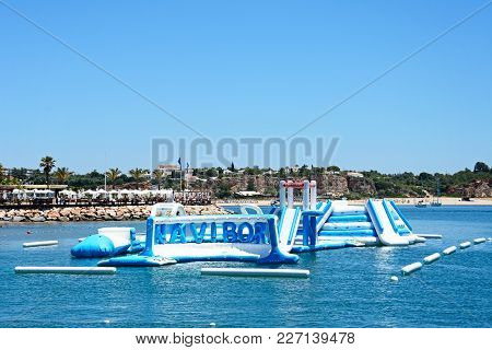 Portimao, Portugal - June 7, 2017 - Inflatable Water Park In The Sea With Tourists To The Rear Enjoy