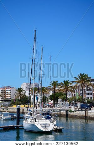Portimao, Portugal - June 7, 2017 - Yachts Moored On The Arade River With City Buildings To The Rear