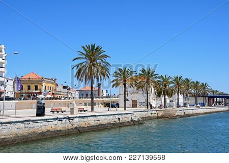 Portimao, Portugal - June 7, 2017 - Palm Tree Lined Promenade Alongside The Arade River With City Bu