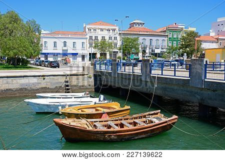Portimao, Portugal - June 7, 2017 - Small Boats Moored Against A Bridge On The Arade River With City