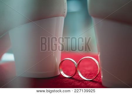 Gold Wedding Rings And White Bride Shoes In Bright Sunlight On A Red Carpet