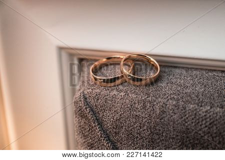 Pair Of Wedding Golden Rings On A Brown Wall Background. Yellow Toned