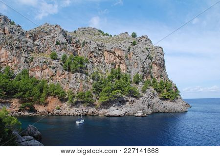 MAJORCA, SPAIN - SEPTEMBER 6, 2017: A yacht moored at the entrance of the port of Sa Calobra on the Spanish island of Majorca. The port is used by visitors to the nearby Torrent de Pareis gorge.