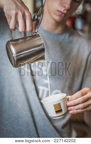 Man Pouring Milk Into Espresso Cup From Above, Making A Steady Stream