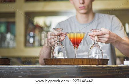Young Bartender Making A Colorful Cocktail, Pouring Alcohol In A Cocktail Glass