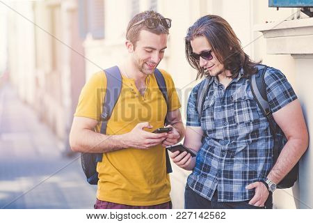 Two Young Men Comparing Phone Models, Using Their Smart Phones, Enjoying Some Funny Internet Content