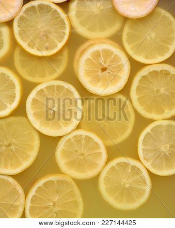 Lemon slices in lemonade. Lemonade background.