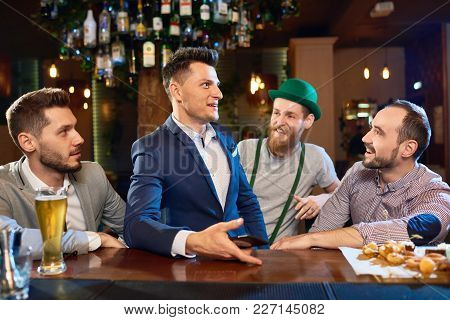 Group Of Cheerful Friends Chatting Animatedly With Each Other While Gathered Together In Pub And Cel
