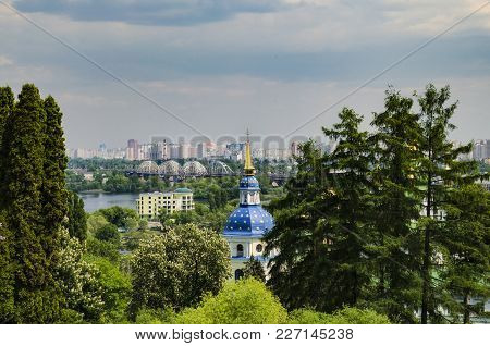 Blue Dome With Golden Stars, Orthodox Church, Surrounded By Trees, Against The Background Of The Bri