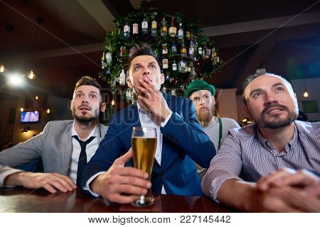 Group Of Concentrated Friends Watching Football Match While Sitting At Bar Counter And Drinking Beer