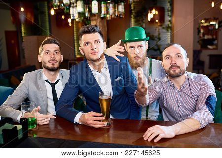 Spending St. Patricks Day With Friends: Group Of Bearded Men Watching Rugby Match And Enjoying Beer