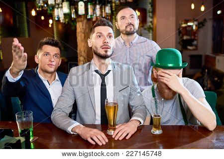Discontent Bearded Men Watching Rugby Match And Drinking Beer While Spending Evening Together, One O