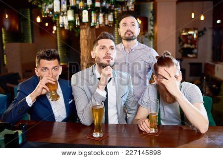 Nervous Bearded Friends Gathered Together In Pub After Work In Order To Watch Football Match And Dri