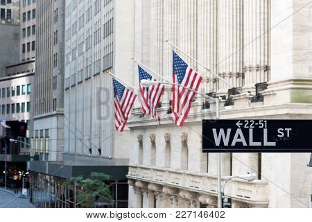 Wall Street Sign In New York City With New York Stock Exchange In Background.