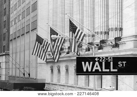 Wall Street Sign In New York City With New York Stock Exchange In Background. Black And White.