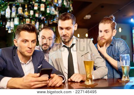 Group Of Surprised Bearded Men Gathered Together In Bar, Drinking Lager And Reading News With Help O