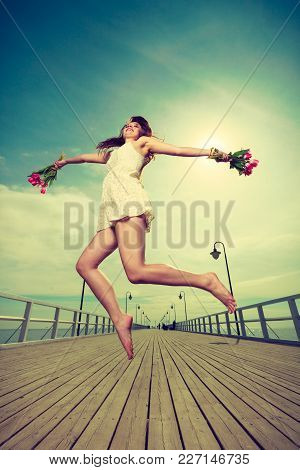 Happiness, Romance, Success Concept. Woman Wearing Short White Dress Jumping On Pier Holding Bouquet