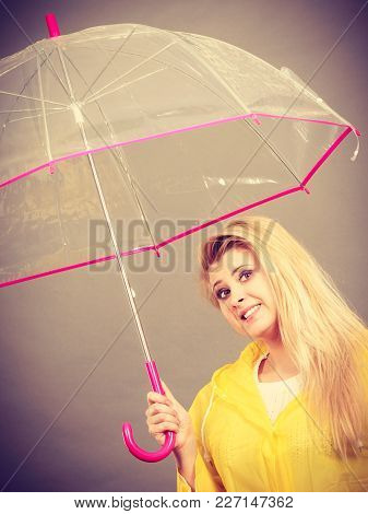 Good Mood During Rainy Day. Happy Blonde Woman Wearing Yellow Raincoat Holding Transparent Umbrella