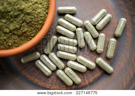 Close Up Green Capsules And Powder On A Clay Brown Plate On A Burlap Rustic Background. Dietary Supp