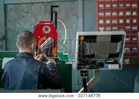 Electrician With Scissor Is Installing Energy System On Machinery Industry, Close Up