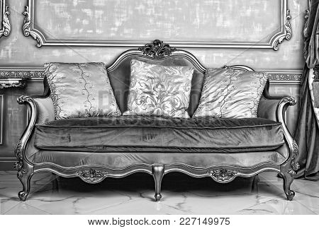 Royal Interior. Living Room With An Antique Stylish Light Sofa With Luxurious Gold Accessories. Bas-