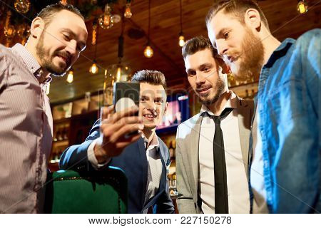 Low Angle View Of Cheerful Friends Looking Through Funny Photos On Smartphone While Spending Evening