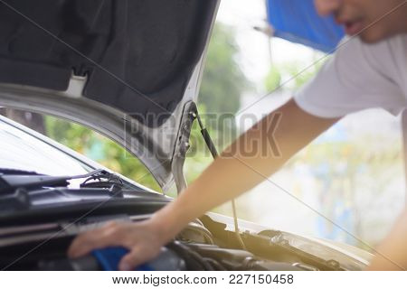 Man Check And Maintenance The Engine Of Car.