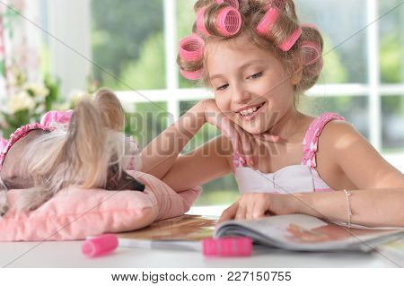 Cute Curly Little Girl With Pink Curlers Sitting At Table And Reading Magazine