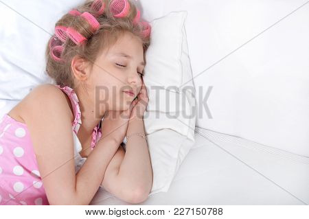 Lovely Little Girl With Pink Curlers Sleeping In Bed At Home