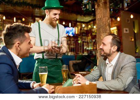 Handsome Bearded Waiter Wearing Leprechaun Costume Taking Order From Two Smiling Businessmen, Interi