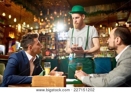 Handsome Young Man Wearing Stylish Suit Sitting At Cafe Table With His Colleague And Making Order Wh