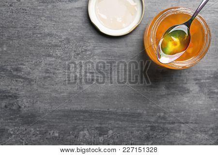 Jar with sweet jam on grey background