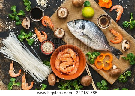 Rustic Background With Asian Food. Ingredients For Cooking. Fish,shrimp,mushrooms, Rice Noodles. The
