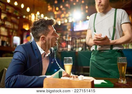 Profile View Of Young Entrepreneur Sitting At Table And Making Order While Spending Evening In Moder