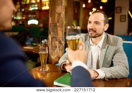 Two Smiling Business Partners Having Informal Meeting In Pub: They Drinking Beer And Discussing Deta
