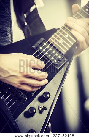 Unrecognizable Hardcore Man Wearing Metal Outfit Playing On Electric Guitar Heavy Rock Music.