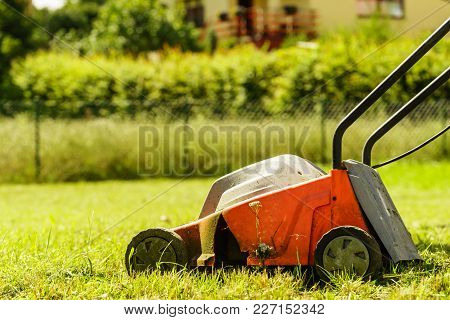 Gardening, Garden Service. Old Lawn Mower Cutting Green Grass In Backyard. Mowing Field With Lawnmow
