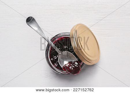 Jar with sweet jam on table