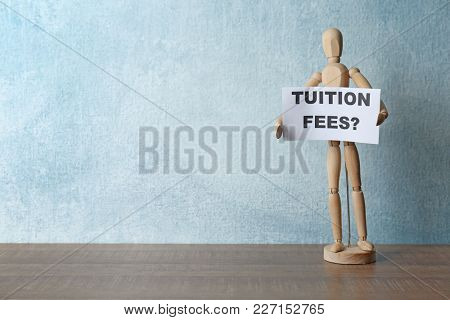 Wooden small mannequin holding paper with question