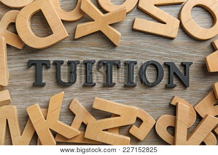Word TUITION made of letters on wooden background