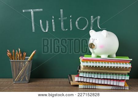 Chalkboard with word TUITION and piggy bank on notebooks